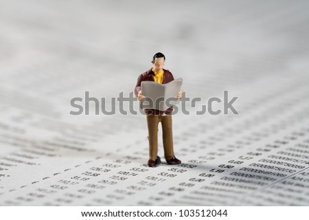 Tiny little model figurine of a private investor standing reading the financials and updated market reports in the paper while standing on a financial document