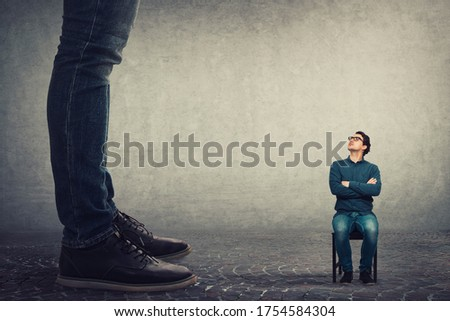 Tiny man employee seated on a chair looking up perplexed at his big boss. Office confrontation, motivation concept. Business person leadership concept. Foto stock ©