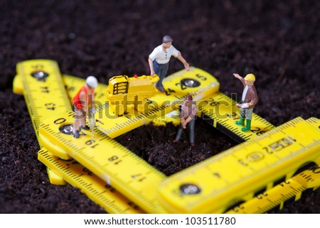 Tiny miniature maintenance team repairing a stylised road with hammer drill and compacting roller while one man works in a pit
