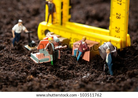 Tiny miniature workmen with their equipment building a house on a rough earth building site with the building frame composed of a bright yellow sectioned ruler