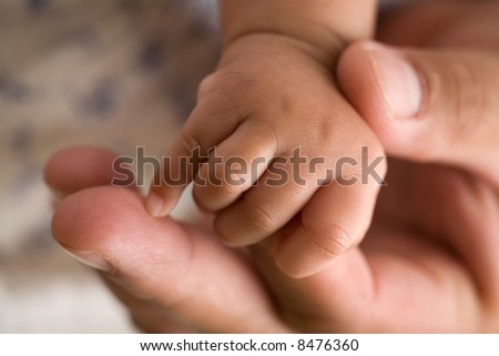 Tiny newborn baby fingers wrapped around adult female fingers up close
