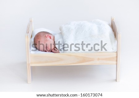 Tiny newborn baby sleeping in a toy crib under a white blanket