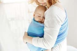 Tiny newborn child close eyes and having good sleep in baby sling feeling protection from his beautiful young mother. Family, lifestyle concept.