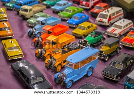 Tiny paper models of different types of automobiles: ambulance, fire-engines, police, lorries & old historic cars. Unfocused #1344578318