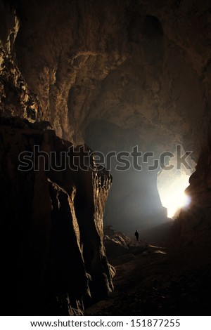 tiny person in huge cave in Laos