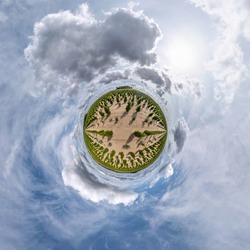 tiny planet in blue sky with sun and beautiful clouds. Transformation of spherical panorama 360 degrees. Spherical abstract aerial view. Curvature of space.