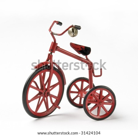 tiny red toy vintage metal tricycle on white background
