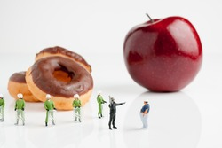 Tiny riot police telling a fat man to eat an apple instead of donuts an obesity concept