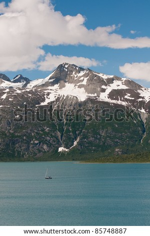 Tiny sailing boat with majestic snowy mountains in background.