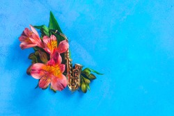Tiny saxophone with spring alstroemeria flowers on a blue background with copy space. Spring or summer musical festival concept with copy space