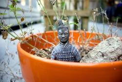 tiny terracotta warrior statue in an orange pot