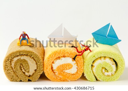 Tiny toys aquanaut diving on the jam roll cake,  paper sailboat.Food background