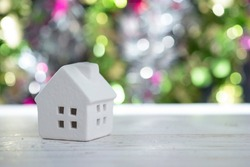 Tiny white house with colourful bokeh background and copy space.