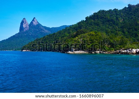 Tioman tropical island in Malaysia. South China sea. Southeast Asia. Tioman Island with Mukut Dragon Horn in the background. Tropical paradise. Summer, holiday, outdoor vacation trip concept. Stock photo ©