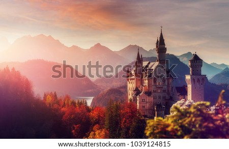 Tipical postcard. Majestic Neuschwanstein castle during sunset, with colorful clouds under sunlight. Dramatik Picturesque scene. fairytale Castle near Munich in Bavaria, Germany. Natural Landscape.