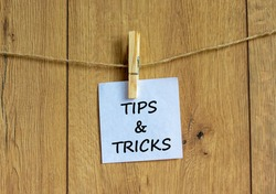 Tips and tricks symbol. White paper on wooden clothespin. Words 'Tips and tricks'. Beautiful wooden background. Business and tips and tricks concept, copy space.