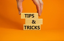Tips and tricks symbol. Wooden blocks with words 'Tips and tricks'. Beautiful orange background. businessman hand. Business, tips and tricks concept. Copy space.