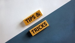 Tips and tricks symbol. Wooden blocks with words 'Tips and tricks'. Beautiful white and blue background. Business, tips and tricks concept. Copy space.