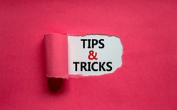 Tips and tricks symbol. Words 'Tips and tricks' appearing behind torn orange paper. Beautiful purple background. Business, Tips and tricks concept. Copy space.