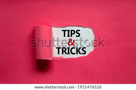 Tips and tricks symbol. Words 'Tips and tricks' appearing behind torn orange paper. Beautiful purple background. Business, Tips and tricks concept. Copy space. Сток-фото ©