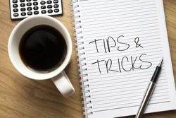 Tips and tricks written on book with wooden background