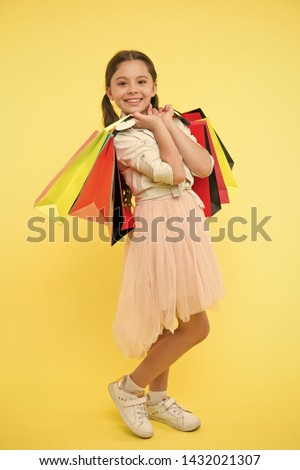 Tips to save money on back to school supplies and clothing. Back to school season teach budgeting basics. Girl carries shopping bags. Prepare for school season buy supplies clothes in advance. #1432021307