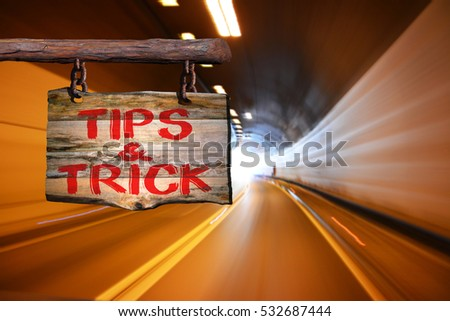 Tips & trick motivational phrase sign on old wood with blurred background