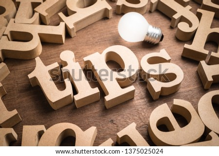 Tips wood word in scattered wood letters with glowing light bulb Stockfoto ©