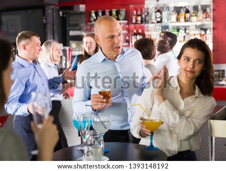 Tipsy man trying to seduce young female colleague on office party at nightclub #1393148192