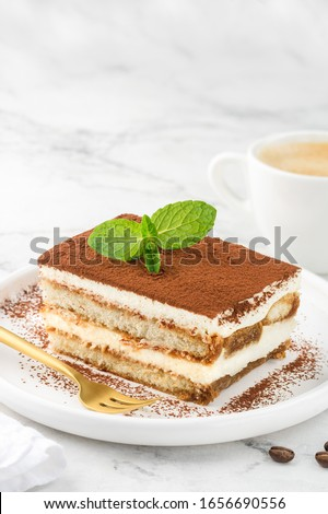 Tiramisu. A slice of a traditional Italian dessert on a white plate and a cup of coffee on a marble table. Selective focus. Copy space Photo stock ©