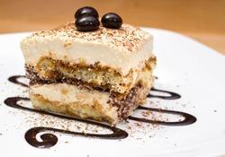 Tiramisu cake and chocolate swirl on white plate