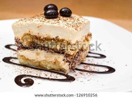 Tiramisu cake and chocolate swirl on white plate
