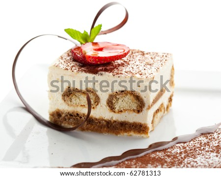 Tiramisu - Classical Dessert with Cinnamon and Coffee. Garnished with Strawberry and Mint