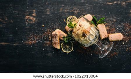 Tiramisu Dessert. Top view. On a black wooden background. Copy space. #1022913004