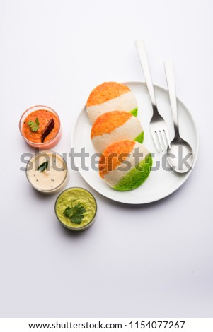 Tiranga Idly or Idli made using Indian National Flag colours like saffron, white and green. Served with colourful chutney. Concept for Happy Independence day greeting card