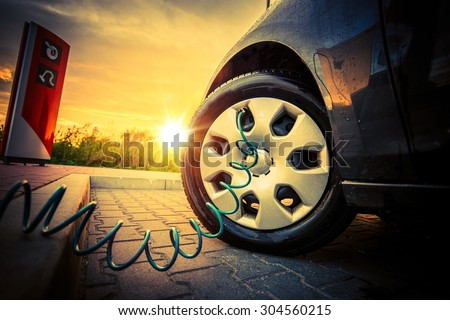 Tire Air Pressure Check at the Check Station During Sunset. Pumping Air into Tire.