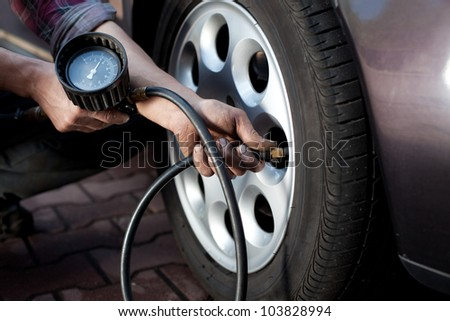 Tire pressure check by car mechanic outdoor