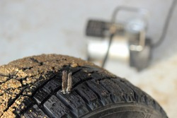 Tire repair thread compound on a car winter tyre close up on wheel pump background, self repair of punctured tire
