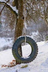 Tire swing hanging from the tree in the winter. Tyre  Swing on Tree in the garden.