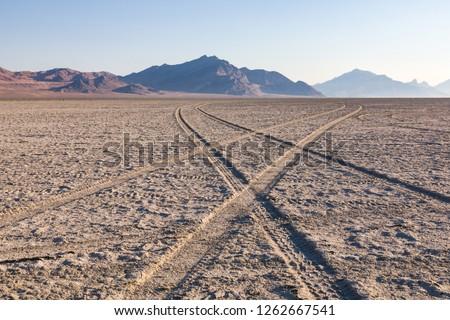 tire tracks criss cross across the bonneville salt flats in the Utah desert of the United States