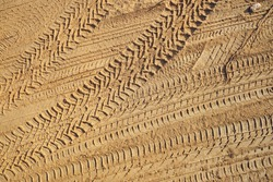 Tire tracks with visible thread on the sand.