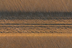 Tire tread marks on sand