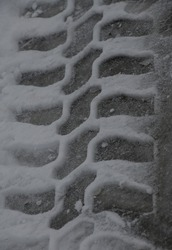 tire treads in snow reminder to put on or take off winter tires shapes and pattern created by car tire tread in early winter snow or early spring thaw road conditions and tire safety vertical format