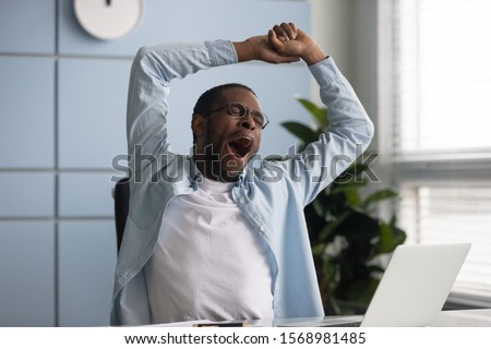 Tired african American male worker yawn stretch in office chair overwhelmed with work at workplace, exhausted biracial young man employee sign feel fatigue after long day, having sleep deprivation