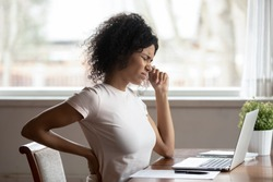 Tired african American millennial female worker sit at desk touch back suffer from lower spinal spasm, hurt unhealthy biracial woman stretch have strong backache, incorrect posture concept