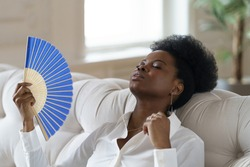 Tired Afro business woman suffering from heatstroke or hot summer flat without air-conditioner, touching her forehead, using waving fan, working on laptop, sitting in living room at home. Overheating