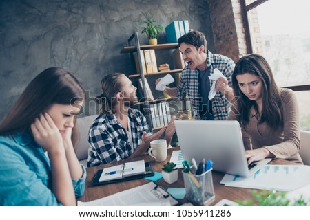Tired aggressive unsatisfied angry mad crazy colleagues are having scandal at workstation and crumpling papers, they want to fight, women are trying to remain silence
