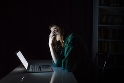 Tired and exhausted young woman hides eyes with hand at laptop pc late in the evening. Portrait of depressed female student or worker sitting in front of computer screen at night, concept of anxiety