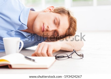 Tired and overworked. Handsome young man lying on the floor and keeping eyes closed