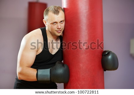 tired and satisfied boxer man after boxing hiting heavy bag at training fitness gym